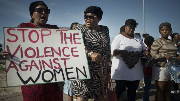 Women hold signs during a protest against ongoing violence against women, in Gugulethu, on May 21, 2016, about 20 Km from the centre of Cape Town.