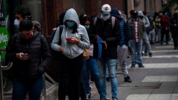 Mengantre di luar kantor yang mengeluarkan tunjangan pengangguran di Santiago, Chile