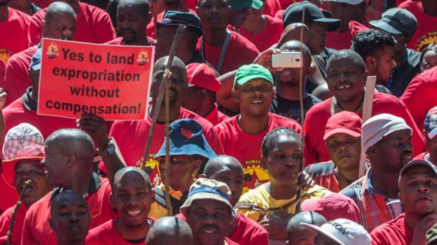 """A demonstrator in South Africa holds a placard reading """"Yes to land expropriation without compensation"""" as thousands of workers take part in a national strike called by the country's second largest labour union - April 2018"""