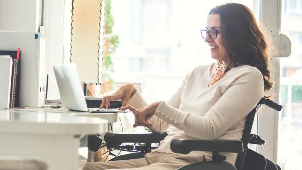 Mujer parapléjica escribiendo en una computadora