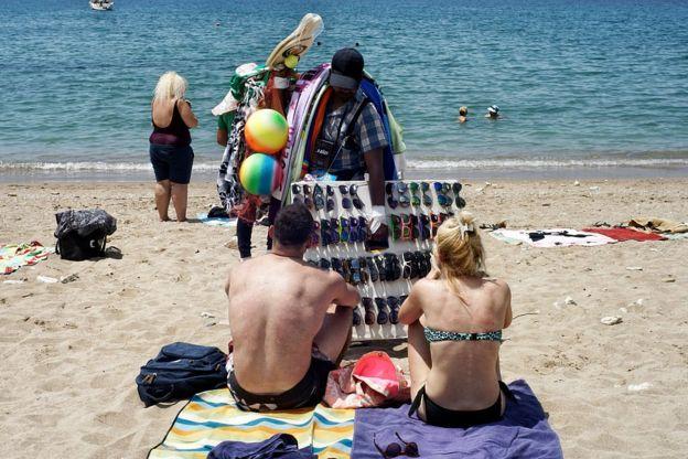 رجل يشتري نظارة شمسية على شاطئ يوناني