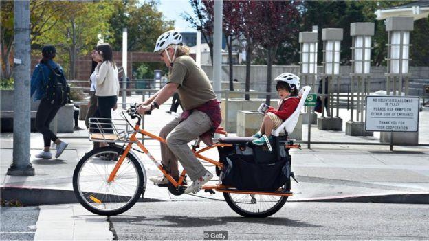 Pai anda de bicicleta com filho