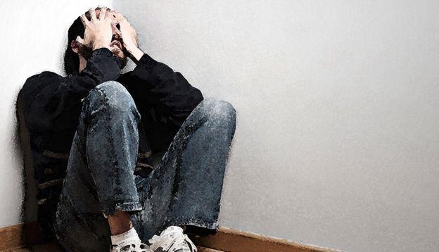 Ilustração de uma foto de um homem sentado no canto de uma sala segurando seu rosto