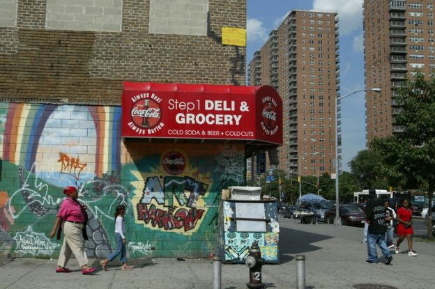 Pedestrians walk past graffiti near public housing in the Harlem neighborhood of New York