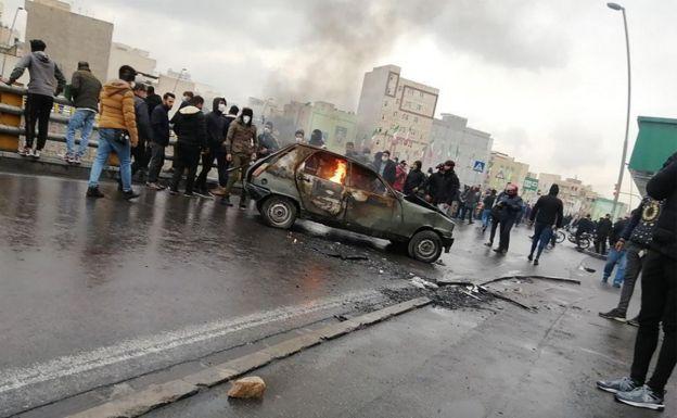 Жители Тегерана возле горящего автомобиля