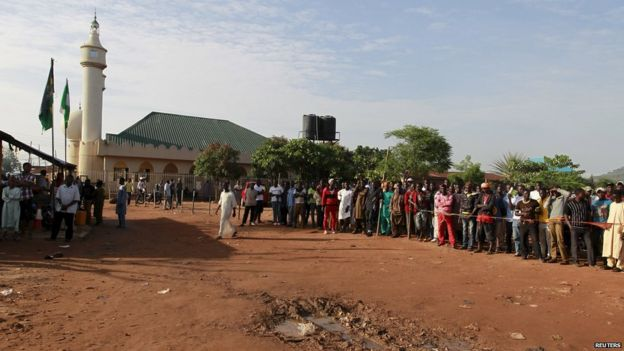 People gather at the site of the blast at Nyanya