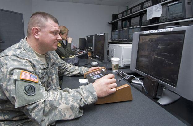 Soldado de la Guardia Nacional frente a monitores de vigilancia.