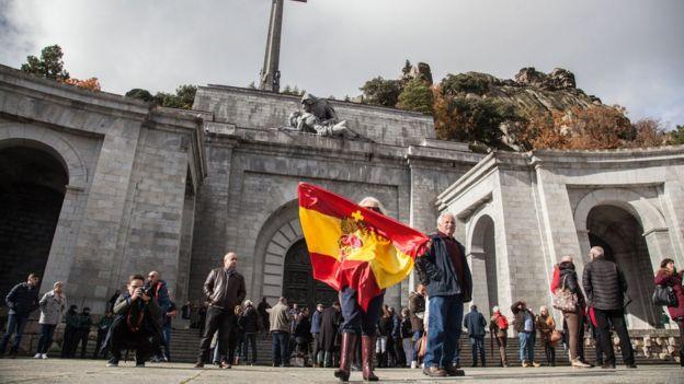 Una mujer ondea una bandera española en las afueras del Valle de los Caídos