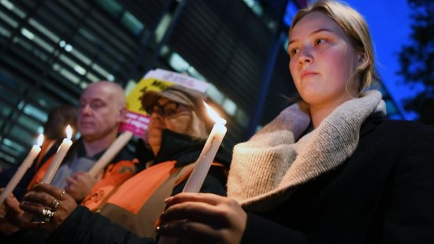 People hold candles at a vigil