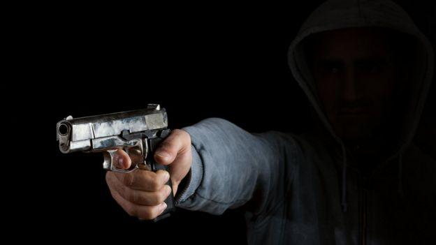 Uma mão com uma arma