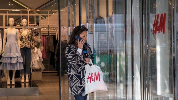 Una mujer sale de una tienda de H&M.