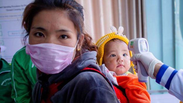 Nhân viên y tế kiểm tra nhiệt độ của một em nhỏ tại biên giới Myanmar và Trung Quốc