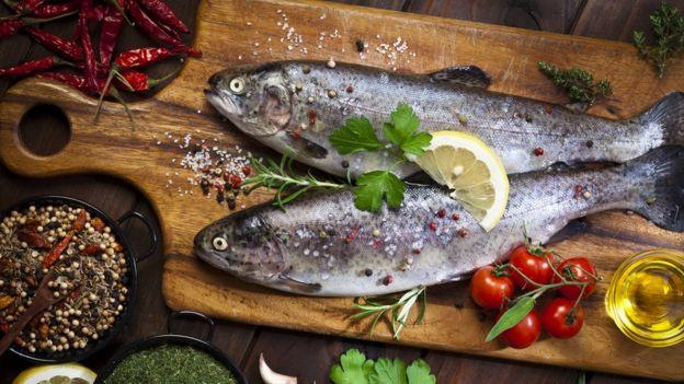 Peixe, ervas e pimenta em uma tábua de madeira.