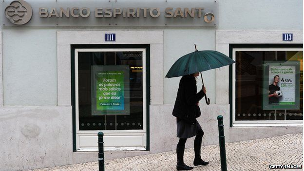 A woman with an umbrella walks past a branch of Bacno Espirito Santo in Lison in May 2011