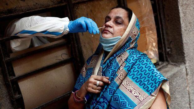Un trabajador médico recolecta una muestra para detectar covid-19 en Nueva Delhi, India.