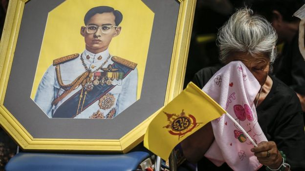 A woman weeps next to a picture of Thai King Bhumibol