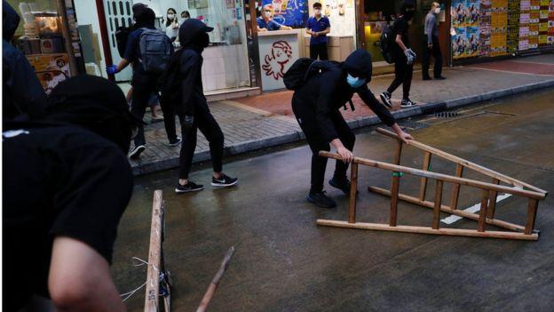 有黑衣示威者在路中央放置雜物。