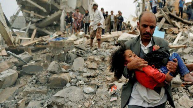 Hombre saca a su hijo de los escombros.