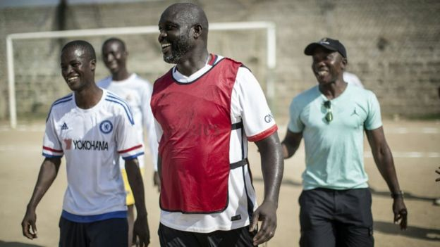 International Liberian football star, George Weah smiles with members of the opposite team after scoring a penalty during a match played on a dusty pitch at the Alpha Old Timers Sports Association in Paynesville in Monrovia on April 30, 2016