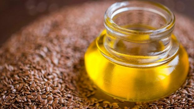 Sementes de linhaça e um vidro cheio de azeite