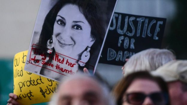 Protesters holding a photo of killed reporter Daphne Caruana Galizia