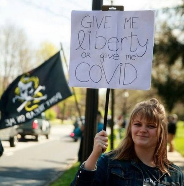"""A protester holds a placard: """"Give me liberty or give me Covid"""""""
