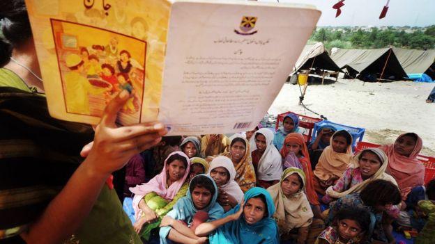Niñas pàquistaníes escuchan mientras su maestra les lee.