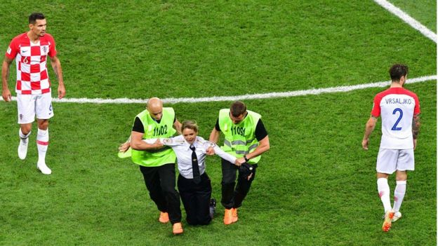 A member of the Russian protest-art group Pussy Riot, is escorted by stewards during the Russia 2018 World Cup final football match