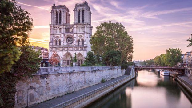 Foto do rio Sena com a catedral ao fundo, do lado esquerdo, sob o céu lilás e laranja do pôr do sol