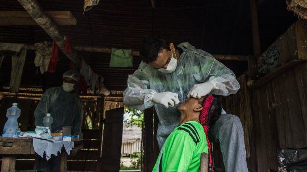 Profissionais de saúde examinam paciente em casa feita de lenha