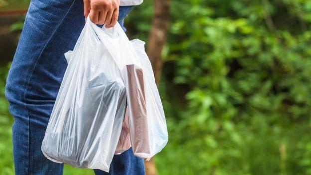 Pessoa levando bolsas de plástico