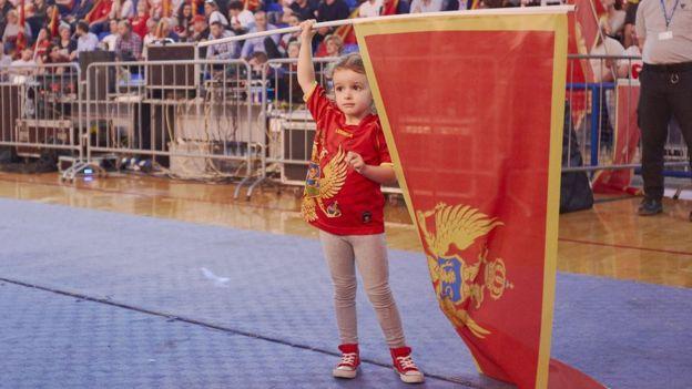 Una niña sostiene una bandera de Montenegro