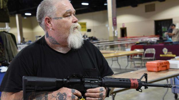 Un vendedor de la feria hace una demostración con el AR-15.