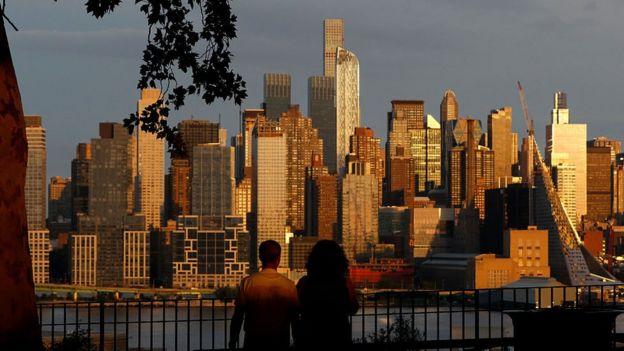न्यूयॉर्क के न्यूजर्सी में सूर्यास्त देखते लोग