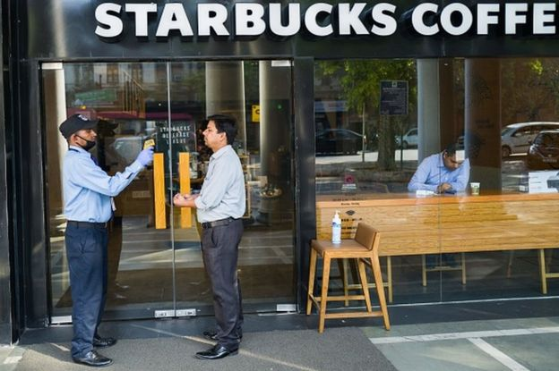 A security guard (L) takes the temperature of a patron as a preventive measure against the COVID-19 novel coronavirus before he enters a Starbucks coffee shop in New Delhi on March 17, 2020