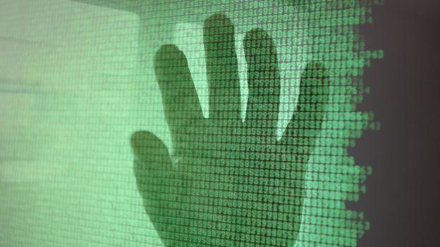 silueta de una mano sobre un código binario