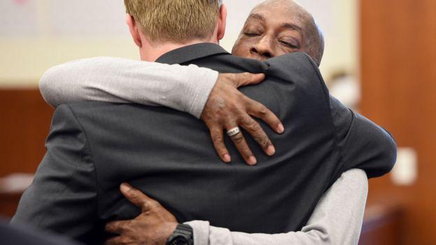 Dewayne Johnson (dir.) abraça seu advogado depois de ouvir a decisão do Juri