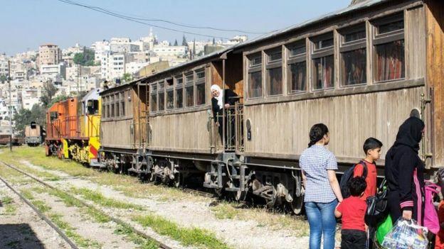 أم وأبناؤها ينتظرون ركوب القطار