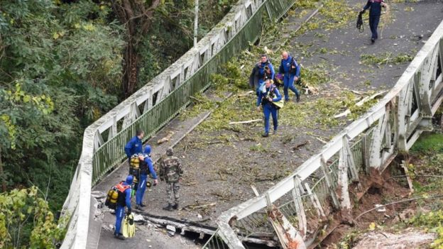Rescuers walk on a suspension bridge which collapsed on 18 November 18 in Mirepoix-sur-Tarn, near Toulouse, south-west France