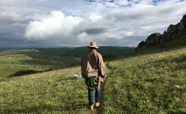 Tshe Bdag Skyabs walking through grass fields towards a lush green valley
