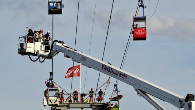 German fire crews evacuate trapped passengers from suspended cable cars that run over the river Rhine after a gondola ran into a support pillar in Cologne, Germany, 30 July 2017