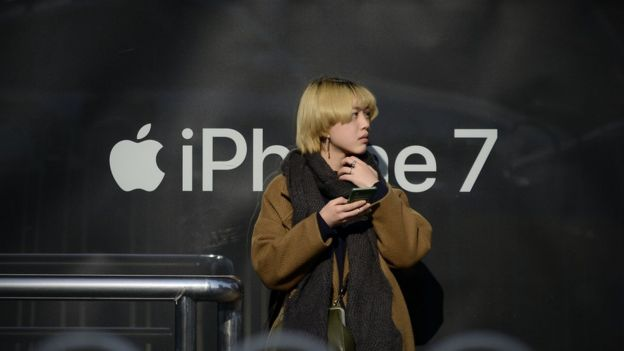 Chinese woman with phone in front of iPhone logo