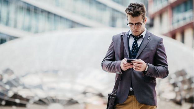 A young man in a suit looks at his cell phone.