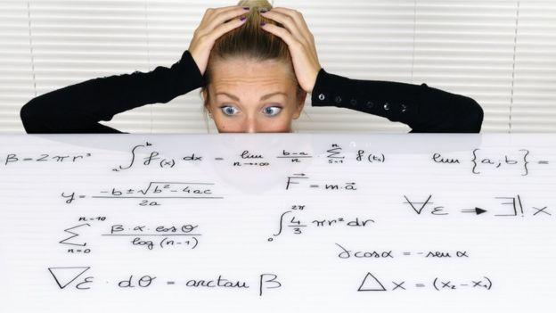 Mujer asustada con un tablero lleno de fórmulas.