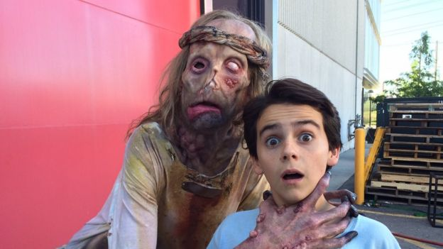 Javier fake-choking one of the children on set of It while in leper costume