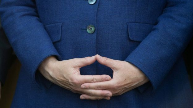 Merkel holds her hands in signature position during a rally. Close up shot of the hands.