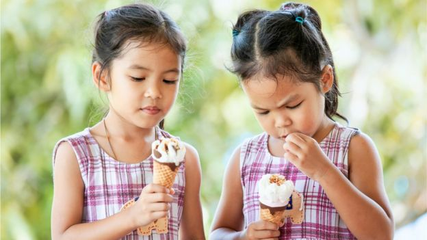Identical twins eating ice cream