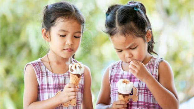 Identical twins eating ice cream