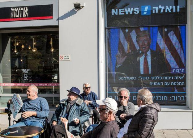 Café en Israel con pantalla con Trump de fondo.