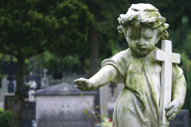 Stone statue of a child holding a cross in a cemetery